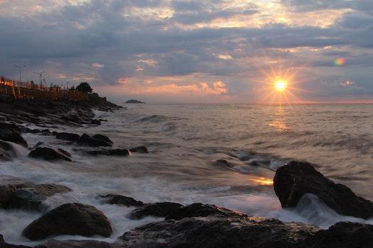 Rocks on Seashore during Sunset