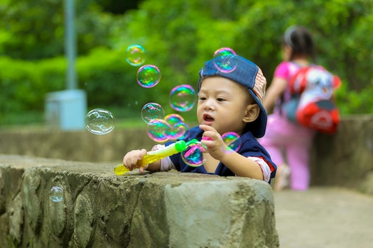 Boy in Blue Fitted Cap Playing Bubbles and Leaning on Grey Concrete Wall at Daytime