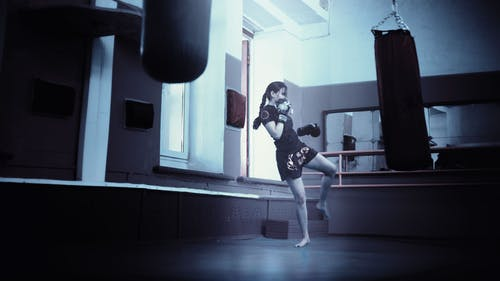 Woman Training in a Gym Kicking a Training Bag
