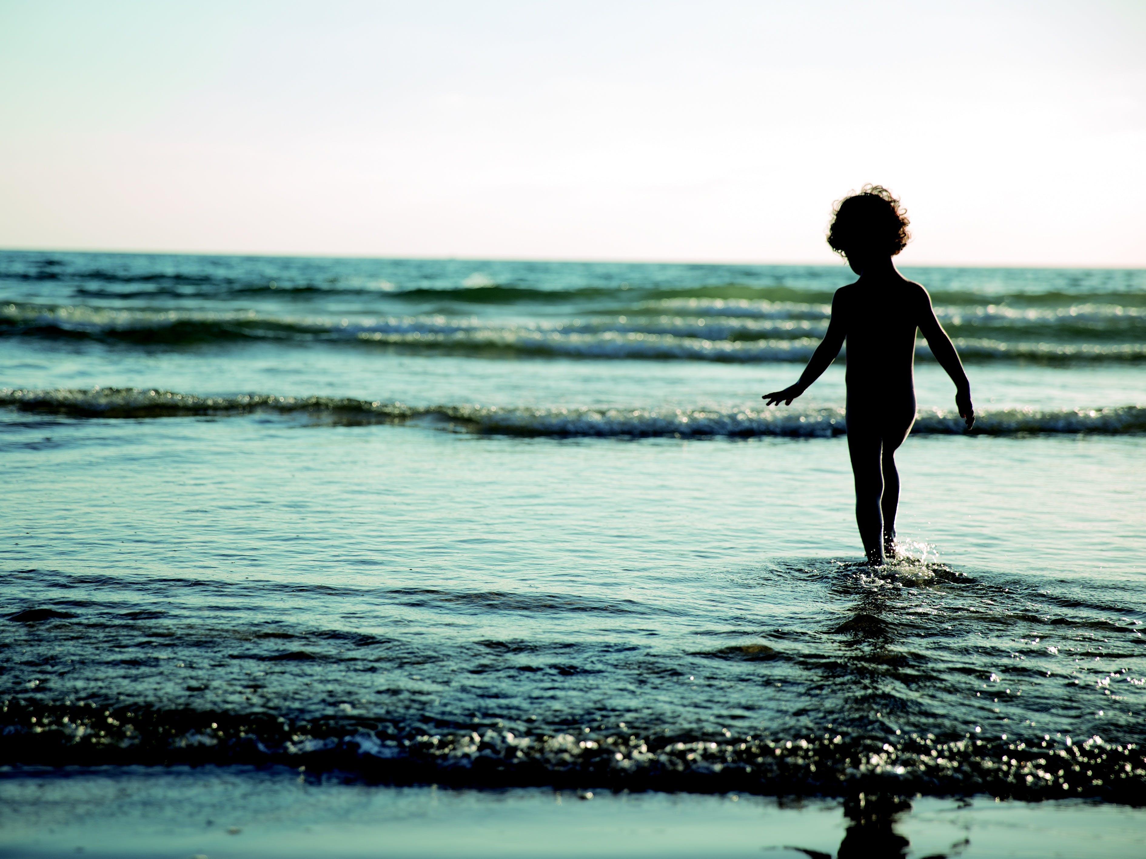 Child Walking on Seashore during Daytime