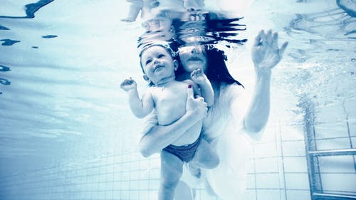 Grayscale Photography of Woman Holding Baby in Swimming Pool