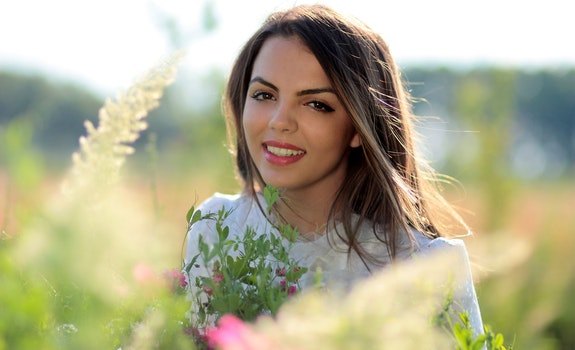Woman in White Crew Neck Shirt Smiling and Surround With Flowers and Plants during Daytime