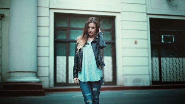Woman in Gray Printed Shirt With Black Leather Jacket and Black Distressed Jeans