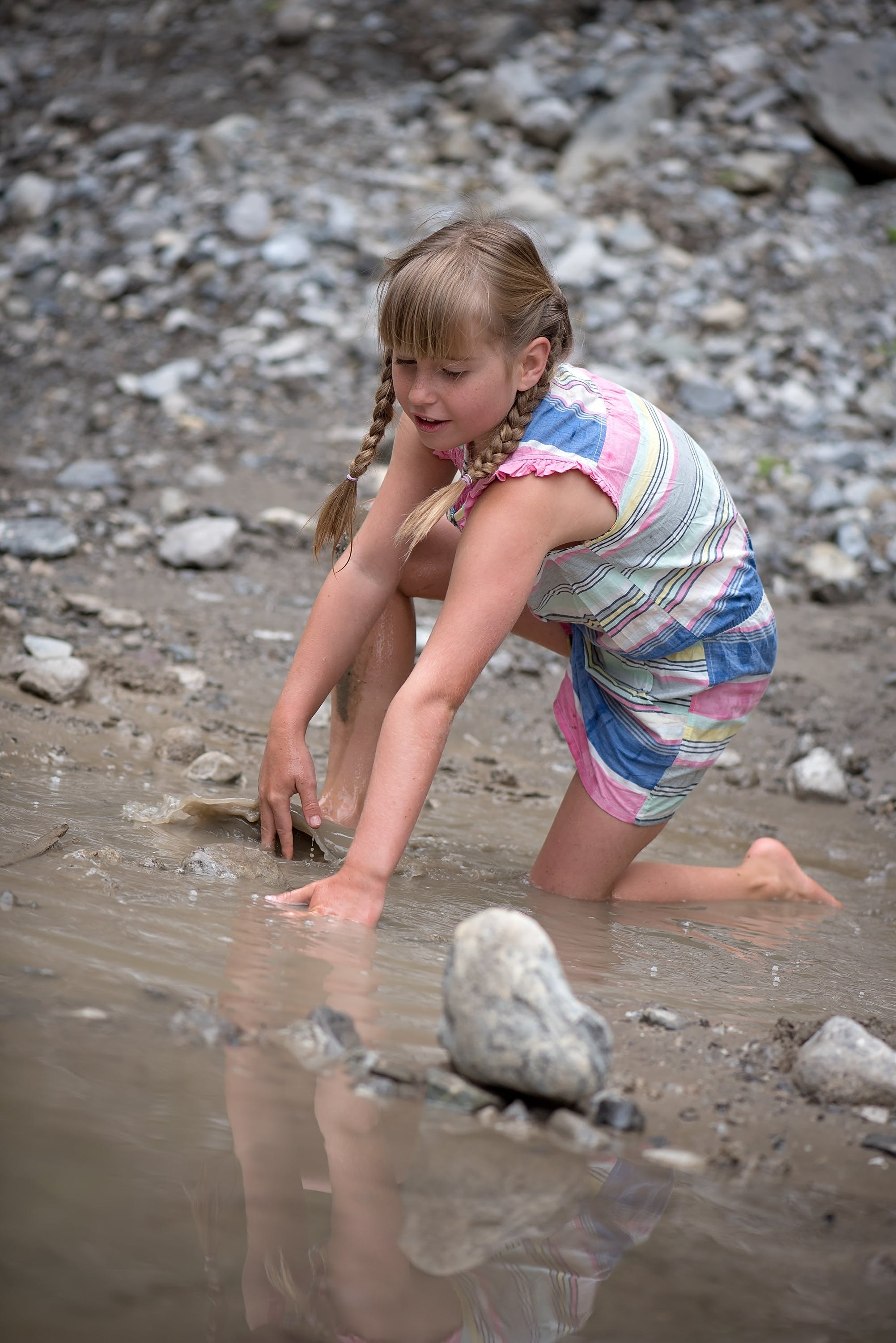 Girl in Pink White and Blue Romper in Body of Water With Gray Rocks