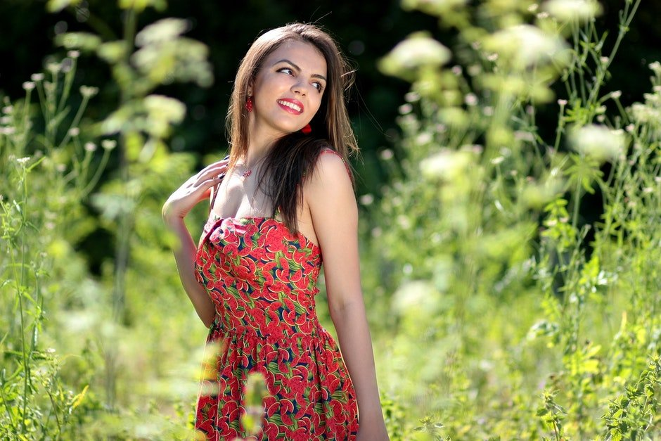 Smiling Woman in Pink Black and Green Floral Tube Dress Near Green Leaf Plants during Daytime