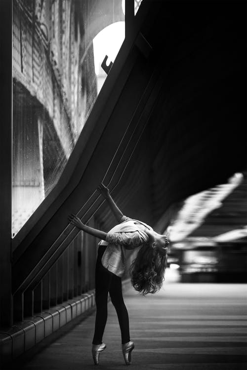 Woman Doing Ballet Dance on Side Walk in Grayscale Photo