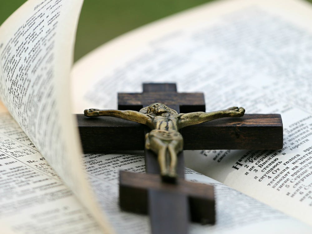 Crucifix on top of the Bible. | Photo: Pexels