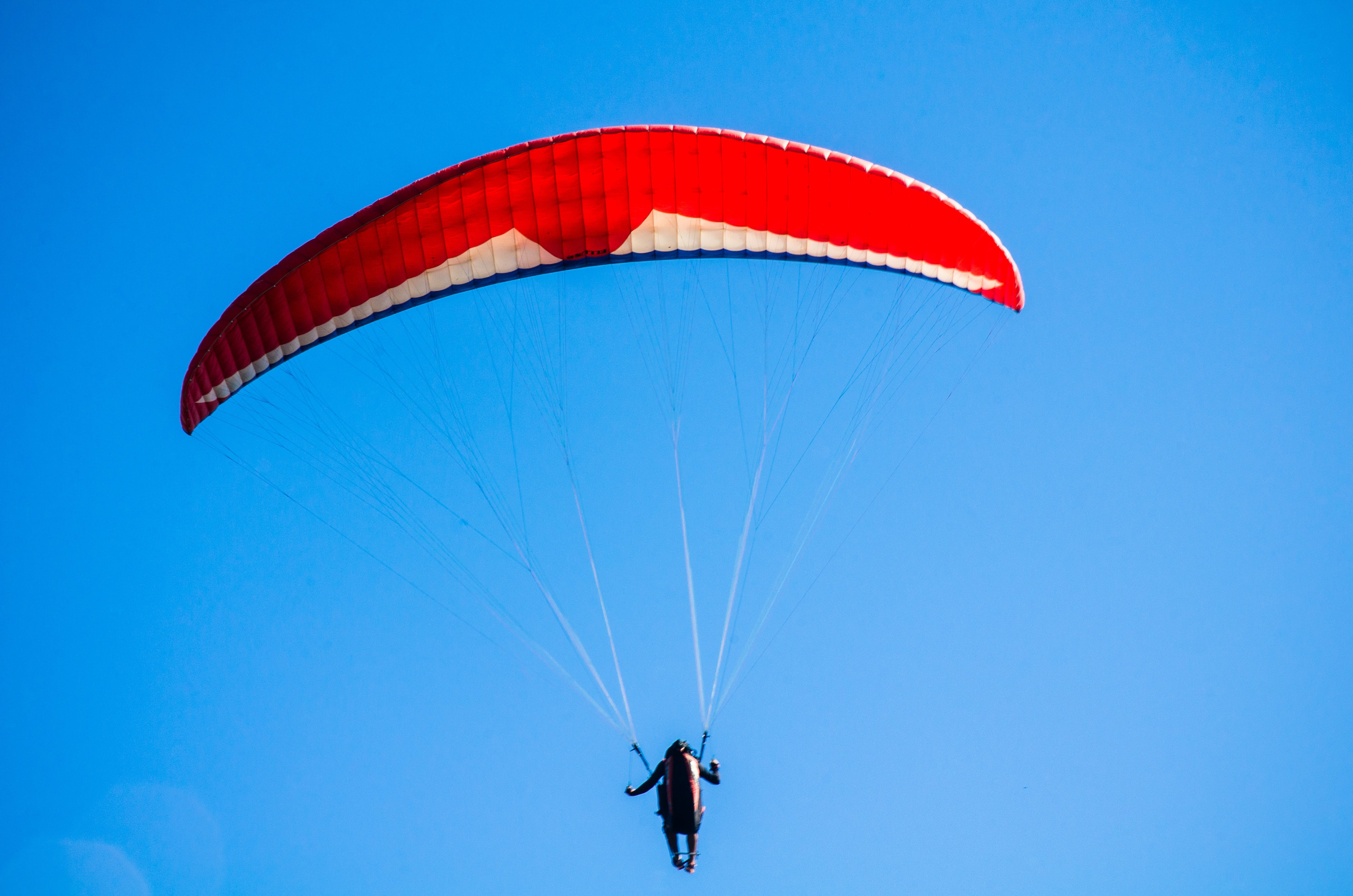 Person Using Red Parachute on Mid Air