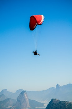 Red White Parachute on Top of Mountains during Daytime