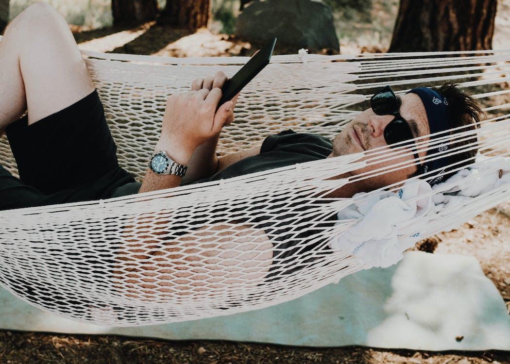 Man Wearing Black Shirt Lying on White Hammock