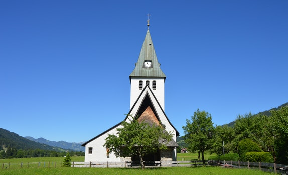 White and Grey Church Near Trees Under Clear Blue Sky during Daylight