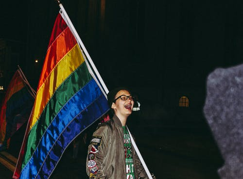 Person Laughing Beside Flag
