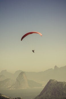 Person in Parachute Gliding Above Mountains
