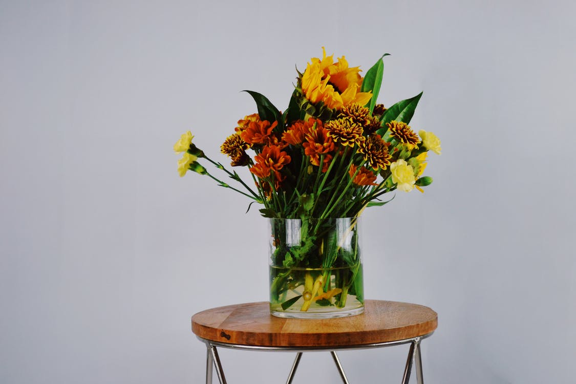 Orange, Red, and Yellow Petaled Flowers in Clear Glass Vase on Round Brown Wooden Table