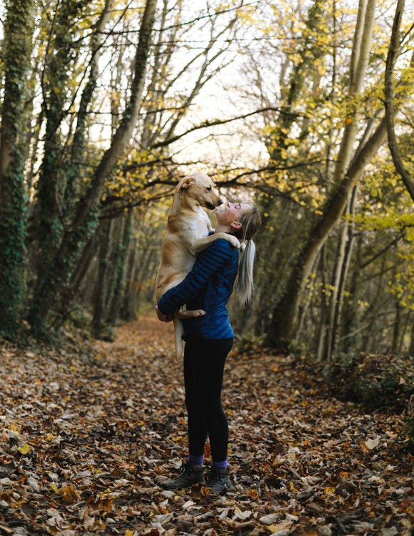 Woman Carrying Dog Outdoors