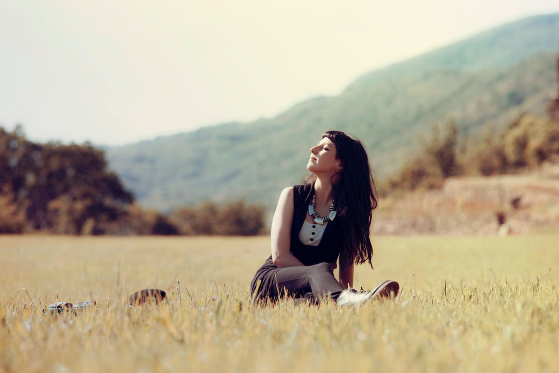 Woman Sitting on Green Grass Field Focus Photography