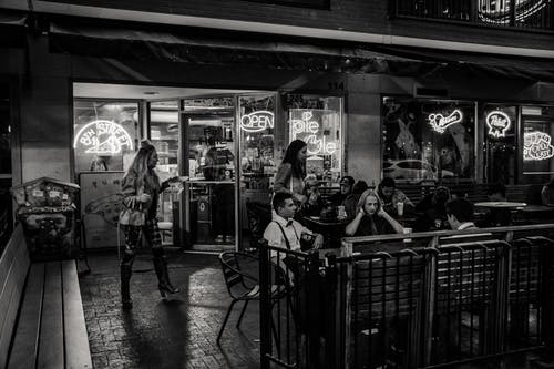 Grayscale Photography of People Near Bar