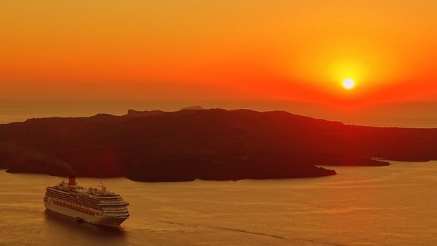 Cruise Ship Traveling on Body of Water Near Island during Golden Hour