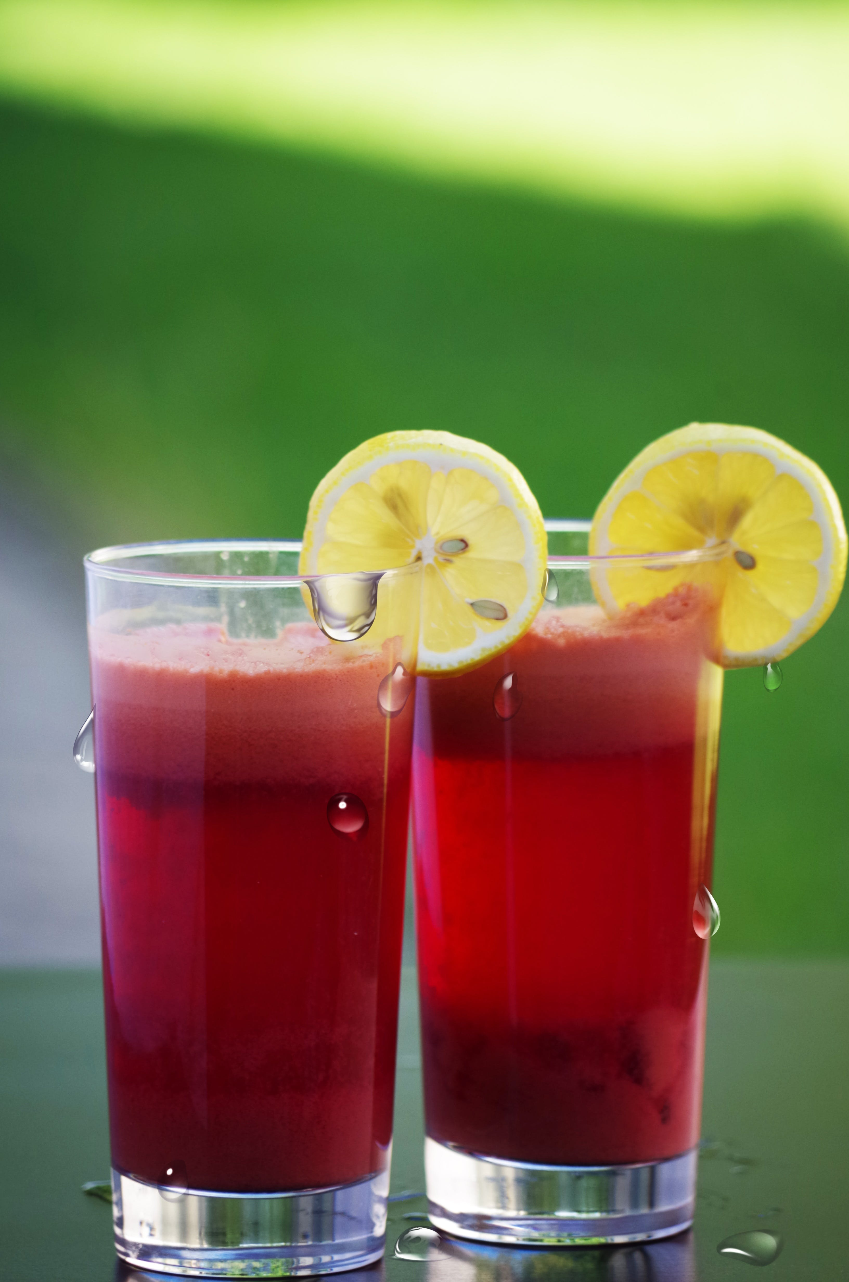 Clear Drinking Glass Filled With Red Liquid With Sliced Lemon
