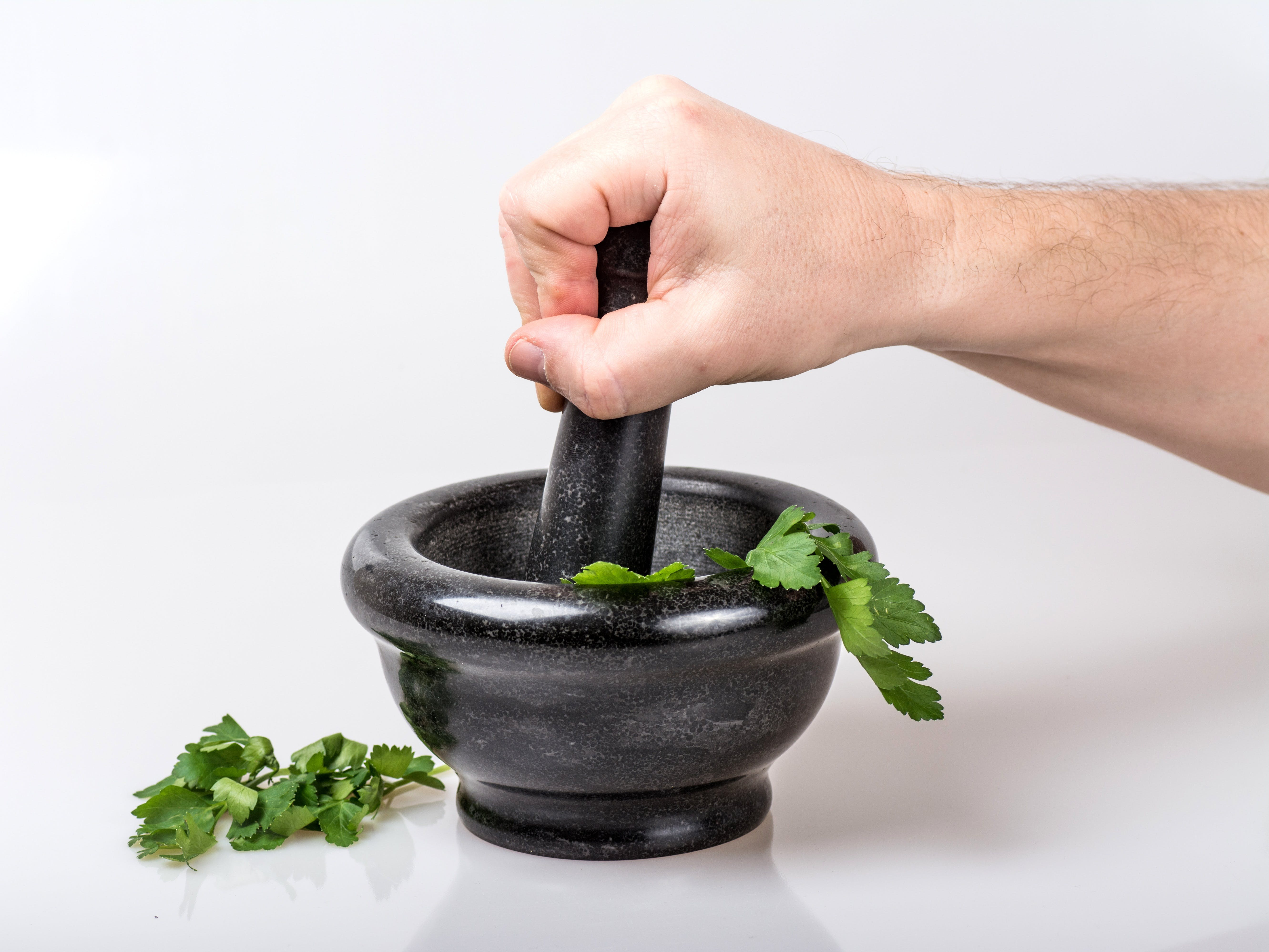 Human Holding Black Ceramic Pestle