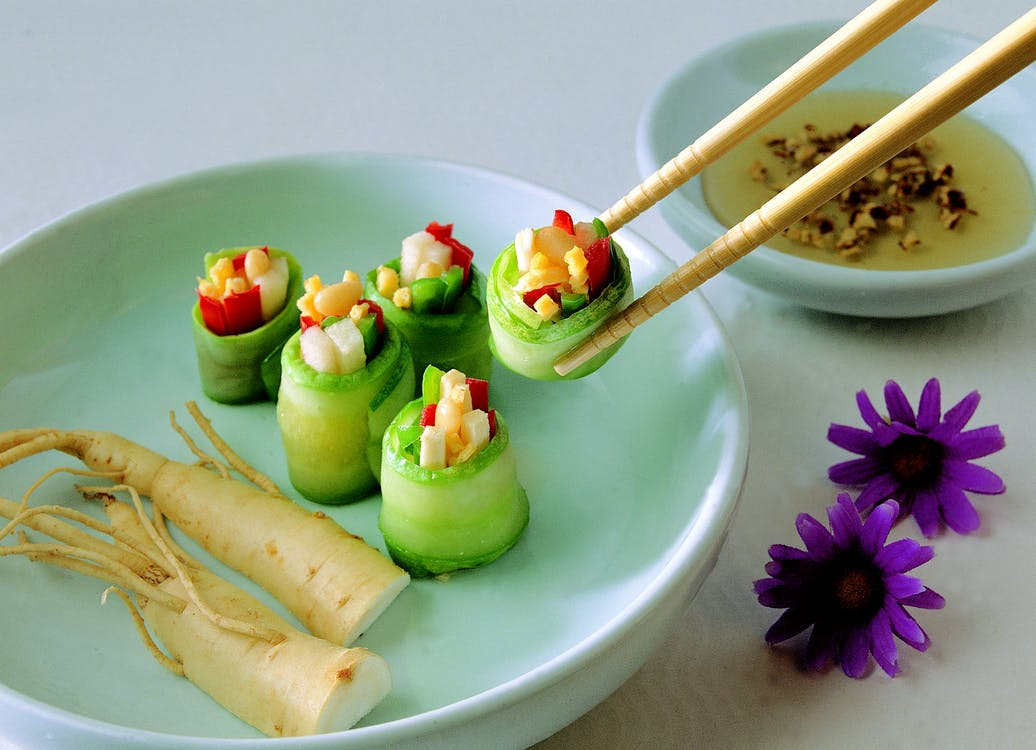 Vegetable Covered With Food Wrapper on Green Bowl With Chopstick Beside Purple Flower