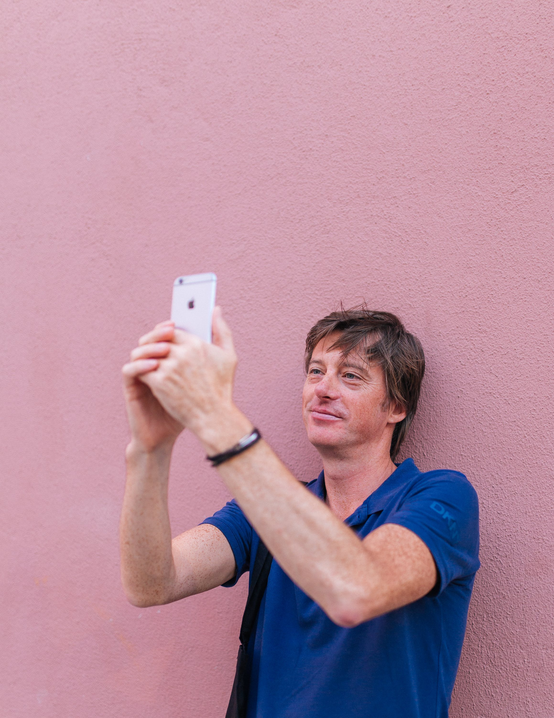 Man Taking Selfie While Leaning on Wall