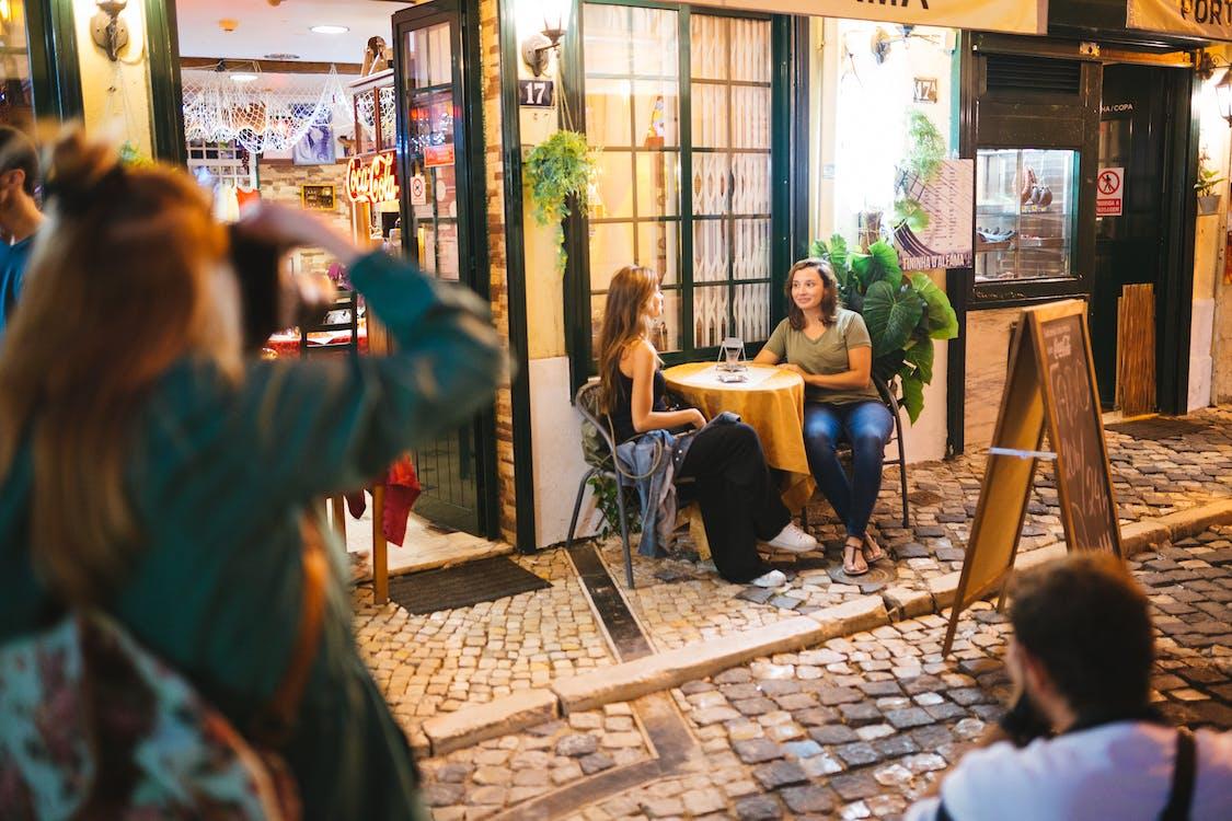 Zwei Mann Und Frau, Die Foto Von Zwei Frauen Machen, Die Neben Rundem Tisch Neben Straße Mit Menübrett Sitzen Und Sprechen