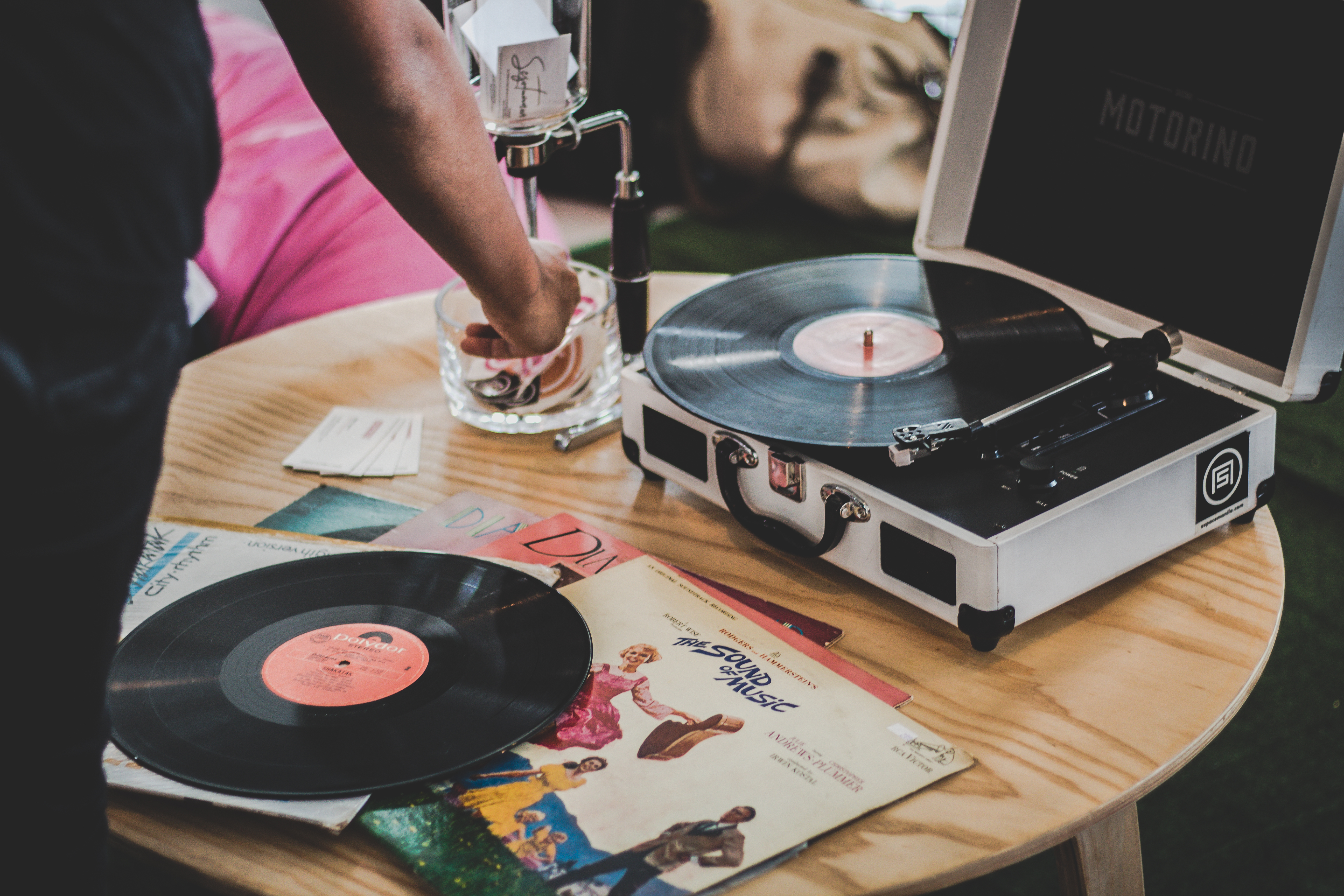 Person Near Vinyl Record Player on Brown Surface