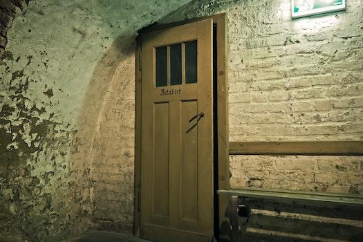 Brown Wooden Door Near White Brick Wall