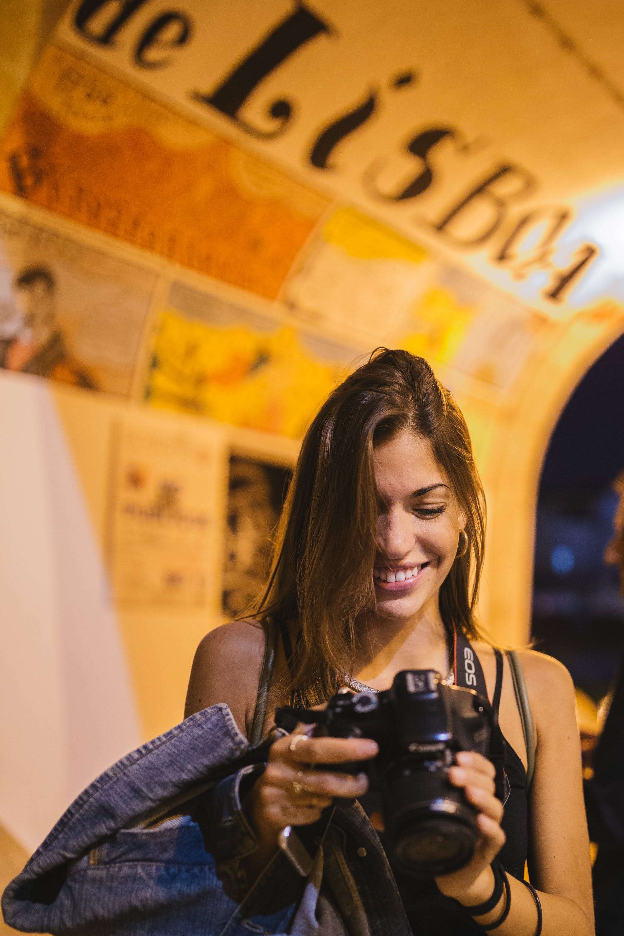 Selective Focus Photography of Woman Smiling Holding Dslr Camera