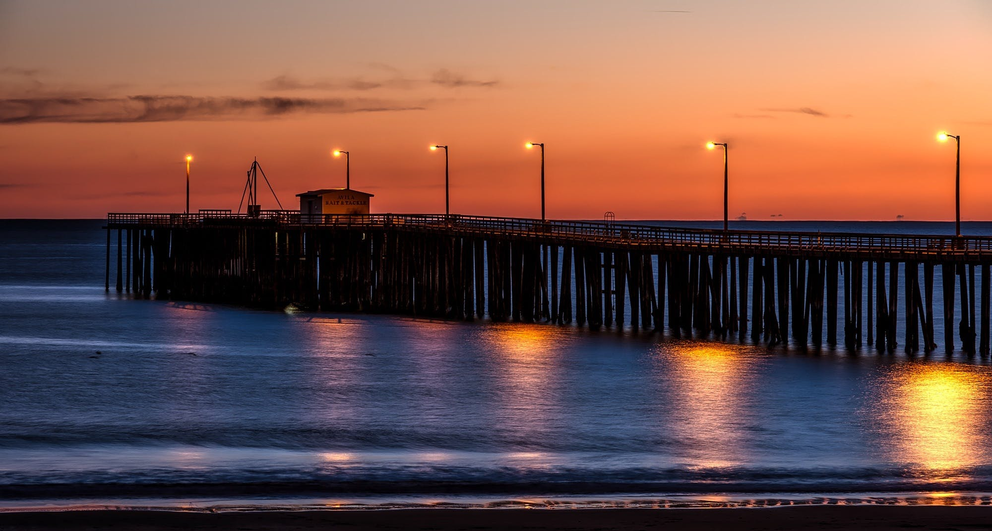 Wooden Dock on Sea Shore With Light Post during Sunset