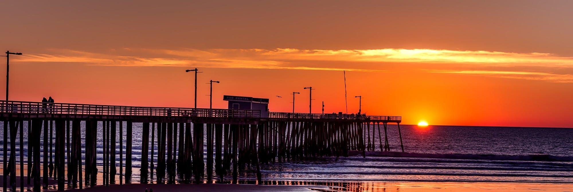 Silhouette of Boardwalk Near Body of Water Under Orange Sunset during Daytime