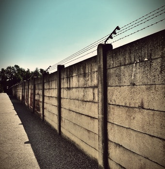 Beige and Black Concrete Wall With Barbwire on Top