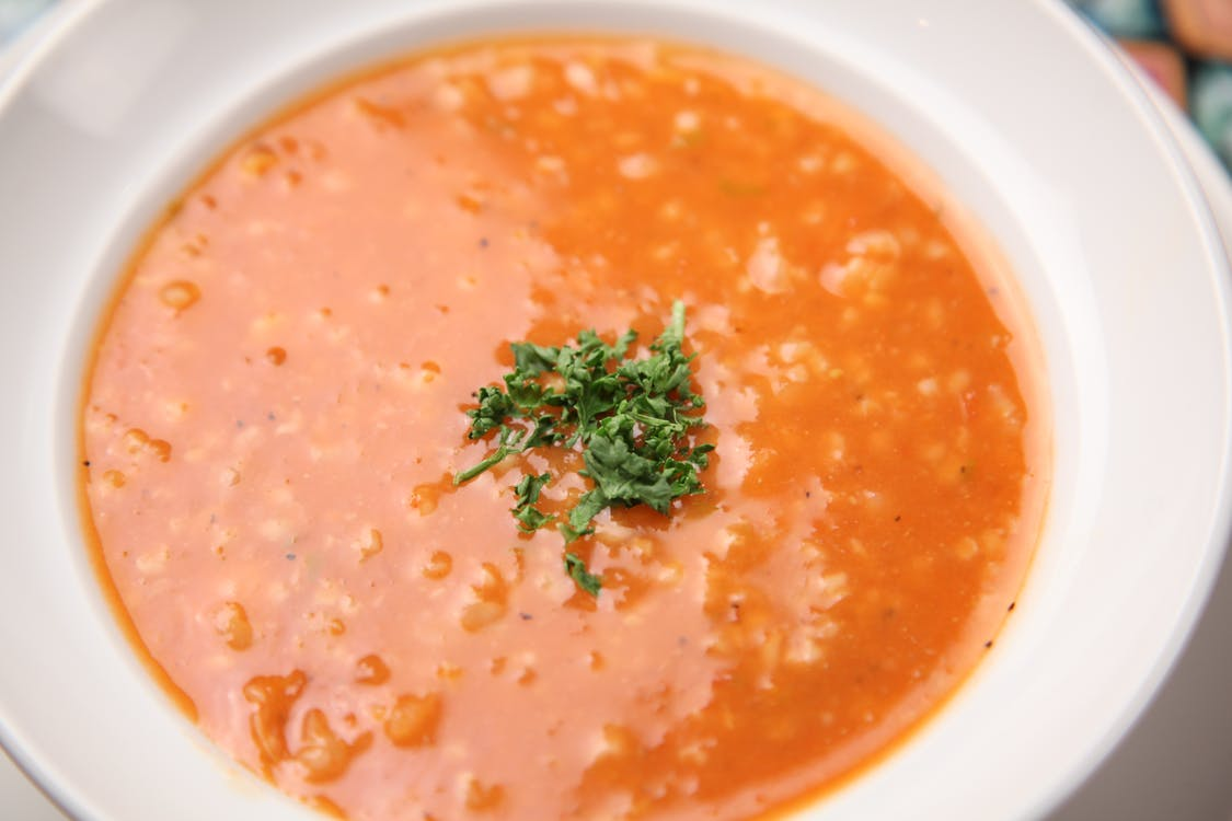 Soup With Minced Herbs on Round White Ceramic Plate
