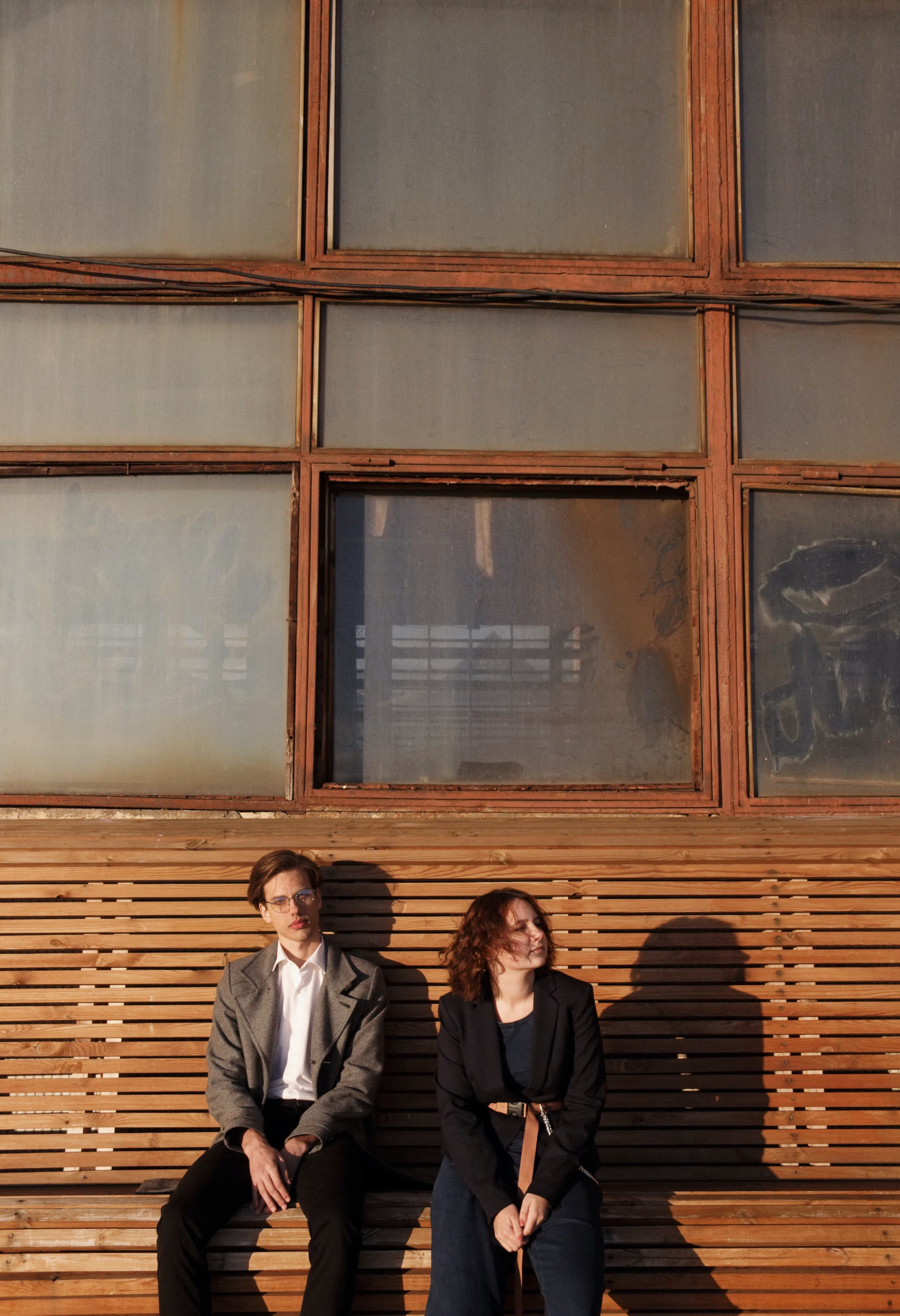 Man and Woman Sitting on Wooden Bench