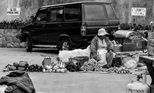 Grayscale Photography Of Person Selling On The Streets