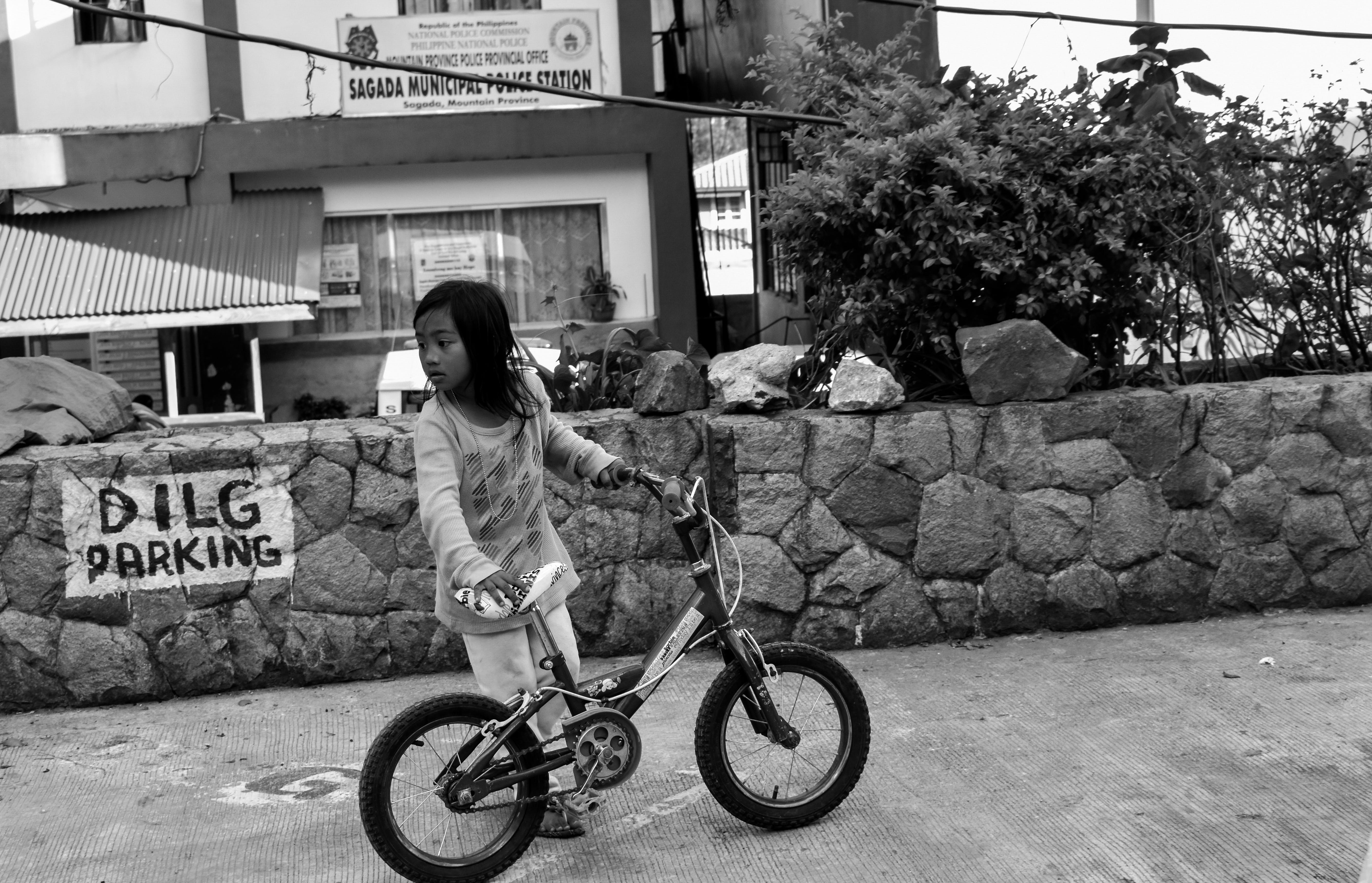 Grayscale Photo of Girl Holding Bike