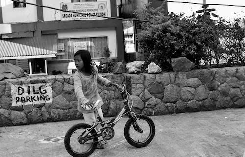 Grayscale Photo of Girl Holding Bike