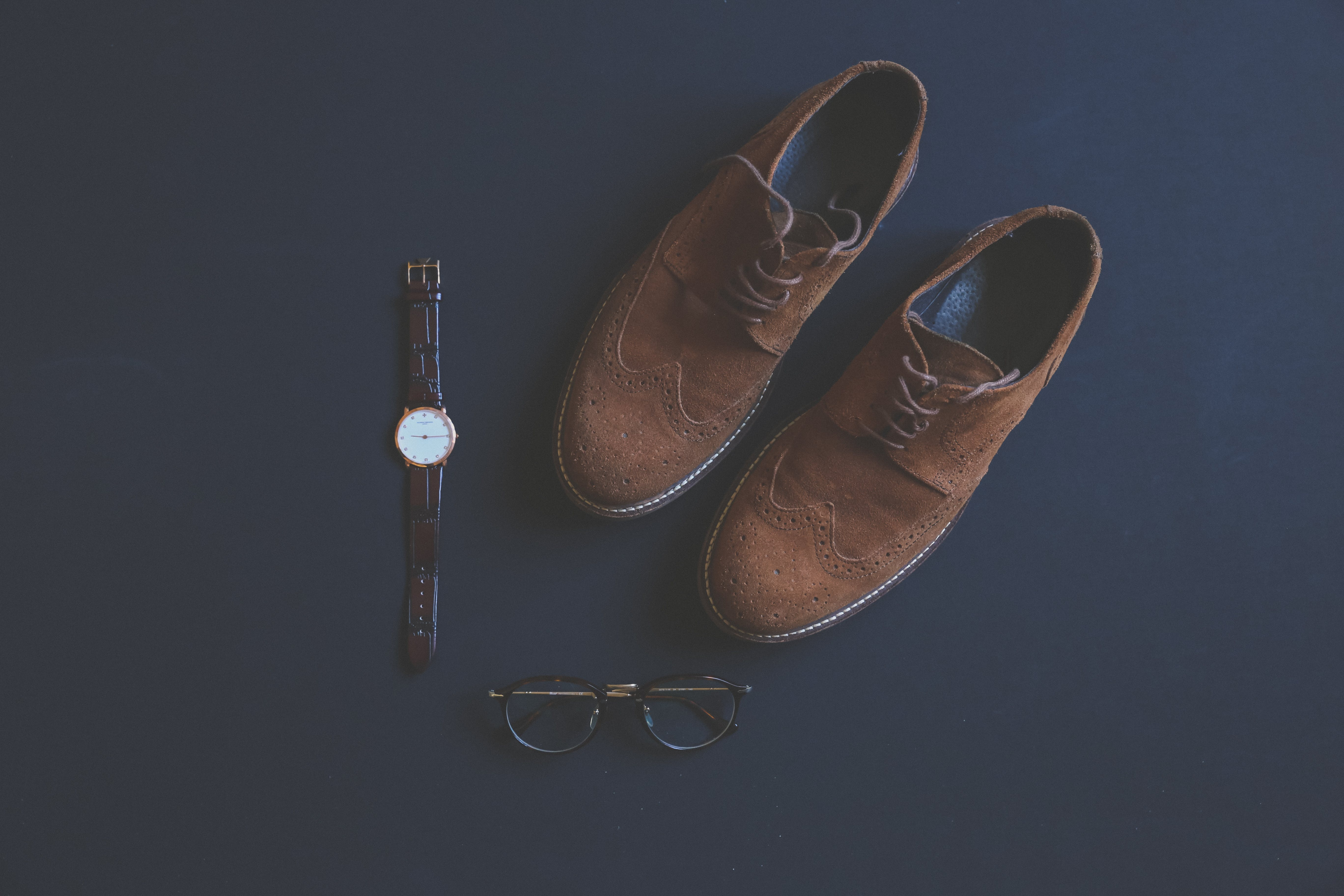 Brown Leather Brogue Shoes Beside Eyeglasses and Watch