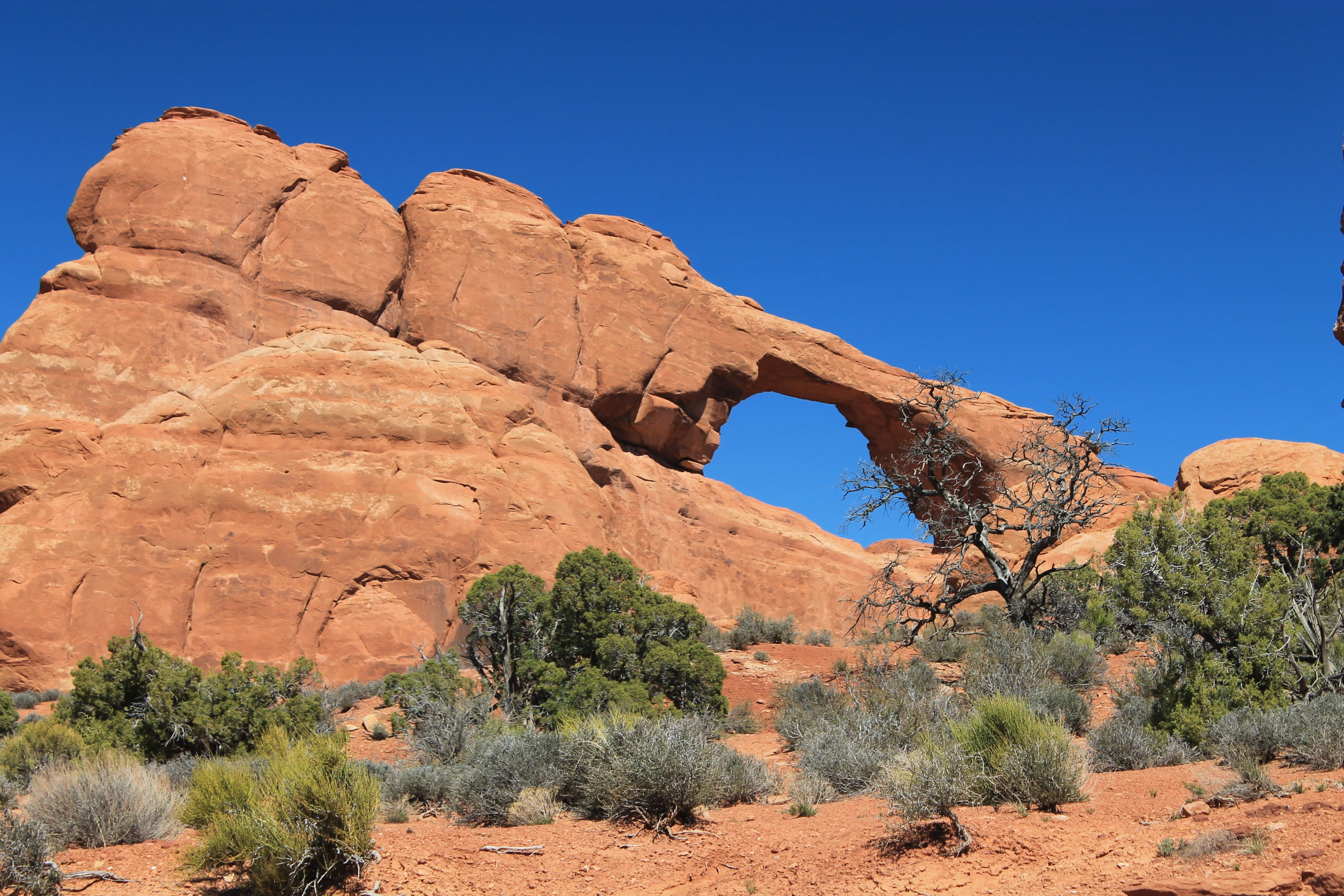 Arc Rock Formation Under Blue Clouds during Daytime