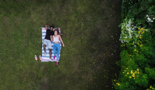 Man And Woman Laying On Blanket