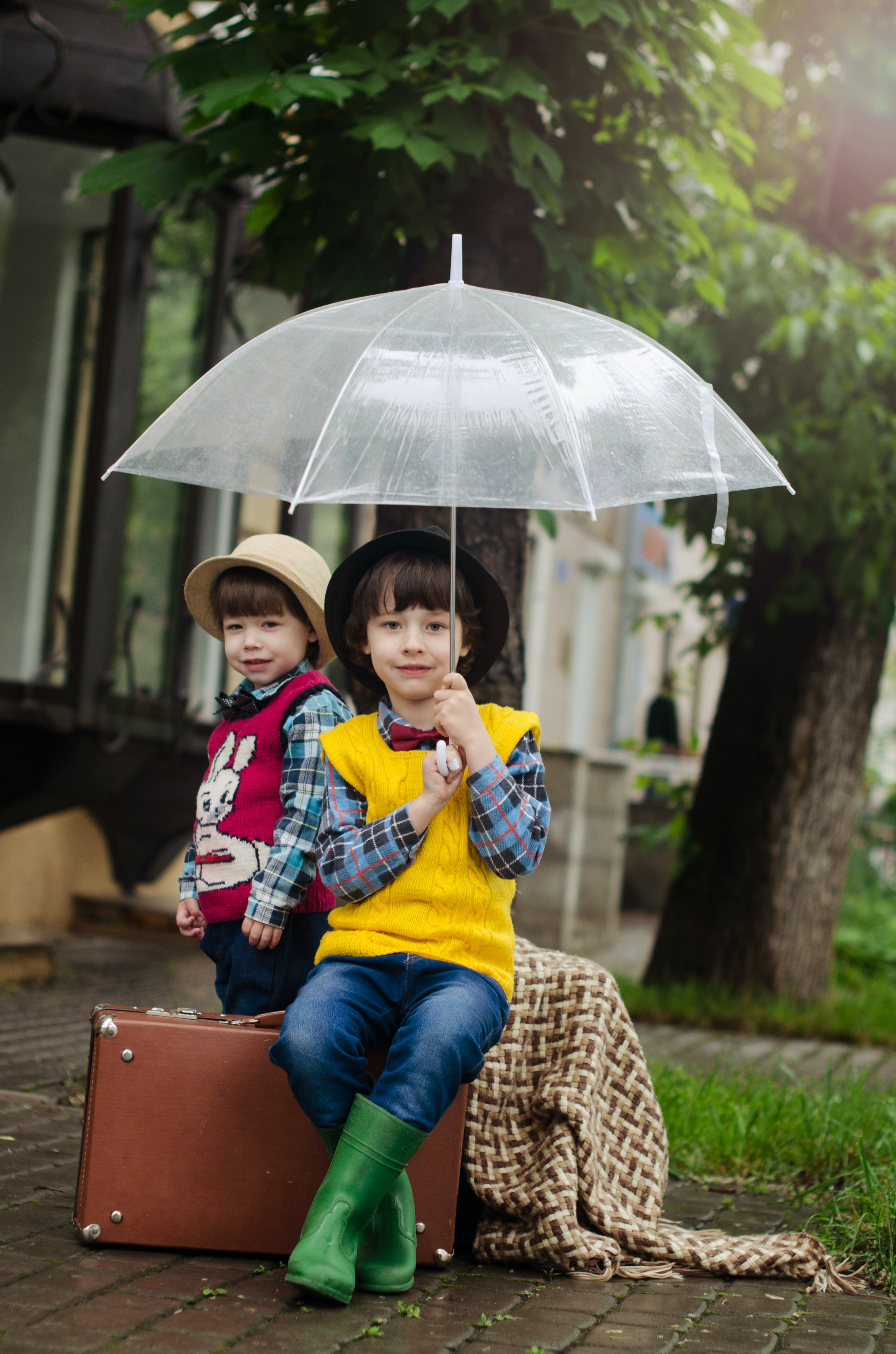 Girl Holding Umbrella While Sitting on Brown Suitcase