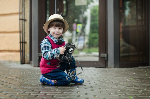 Shallow Focus Photography of Kid Holding a Camera