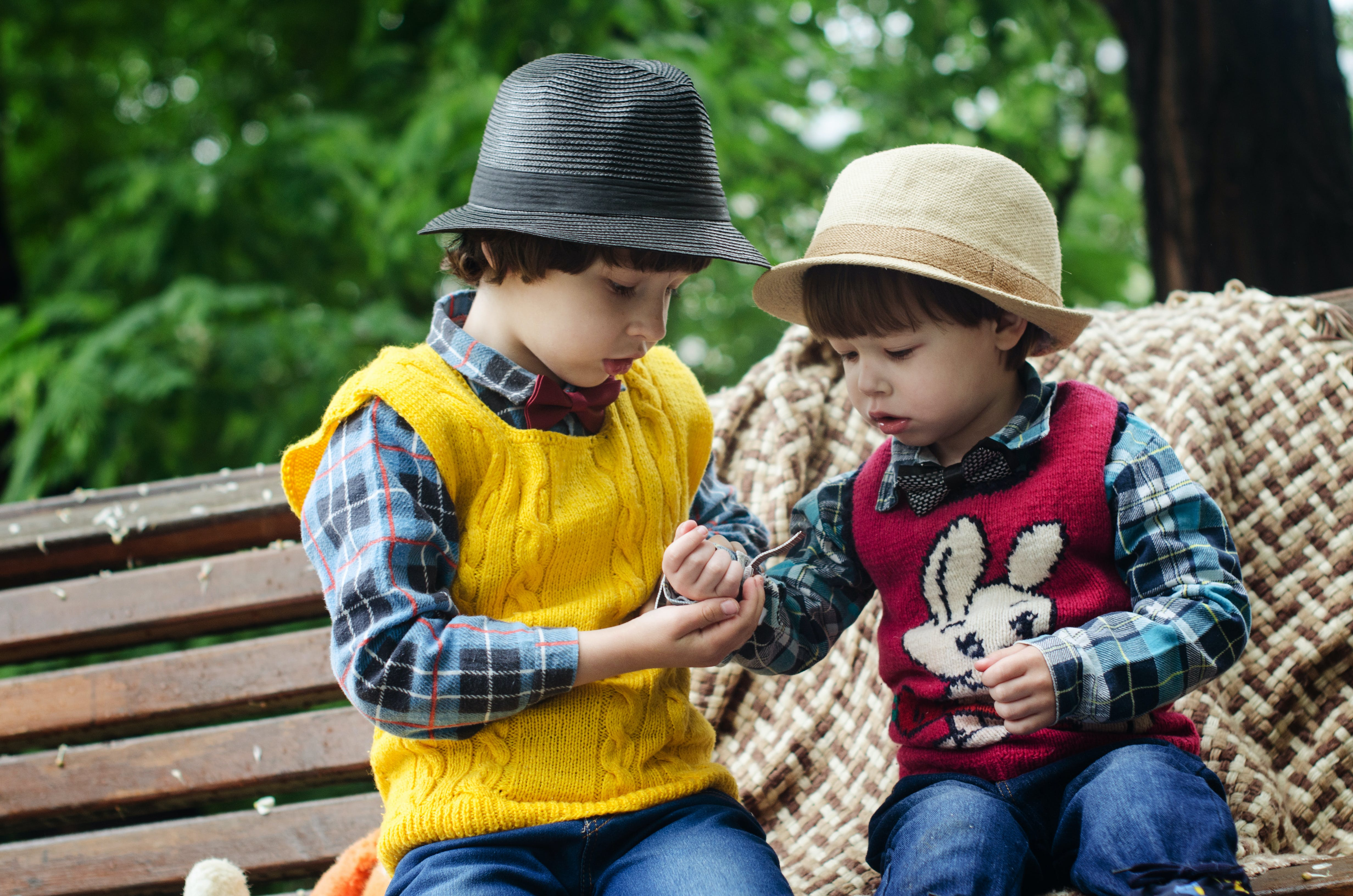Two Boys Sitting on Bench Wearing Hats and Long-sleeved Shirts