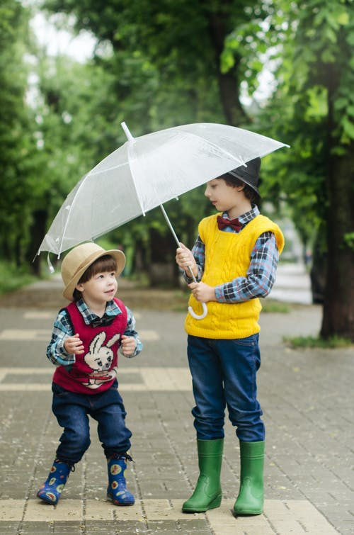 Toddler Holding Umbrella Beside Girl