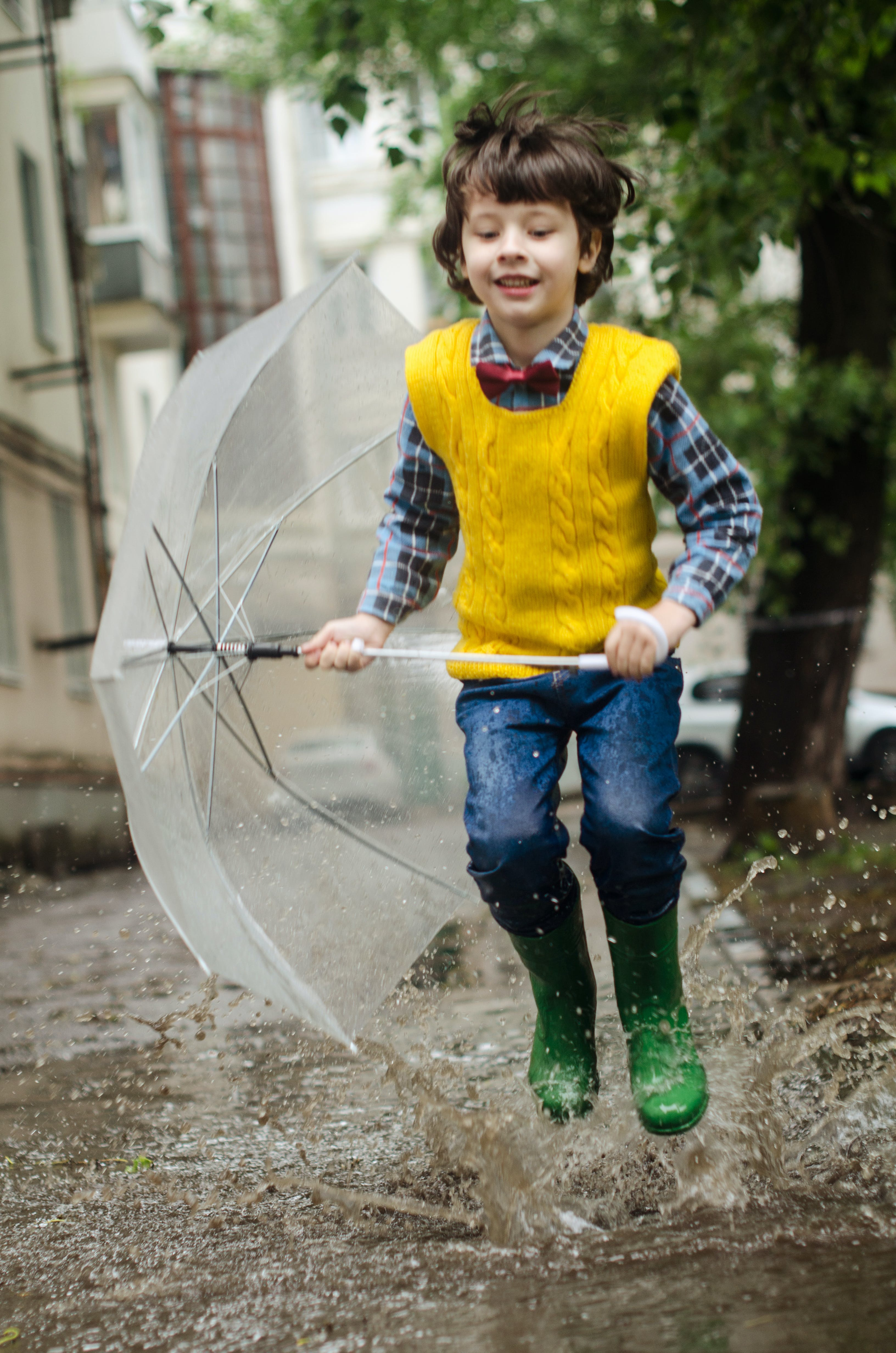 Boy Holding Umbrella While Smiling and Running