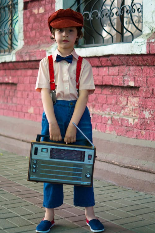 Photo of Boy Holding Radio and Standing Beside of Red House