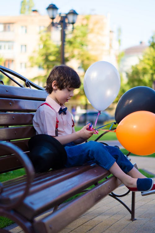 Boy Sitting On Bench While Holding Balloons