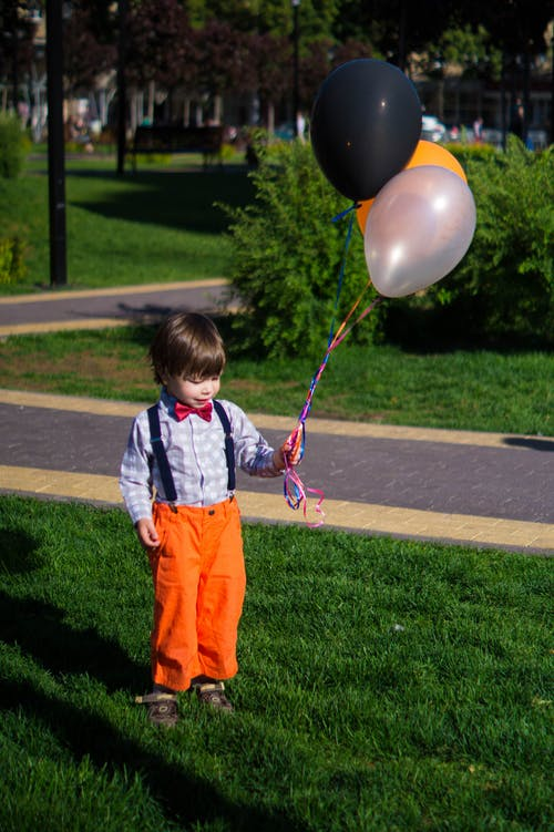 Photo of Boy Holding Balloons