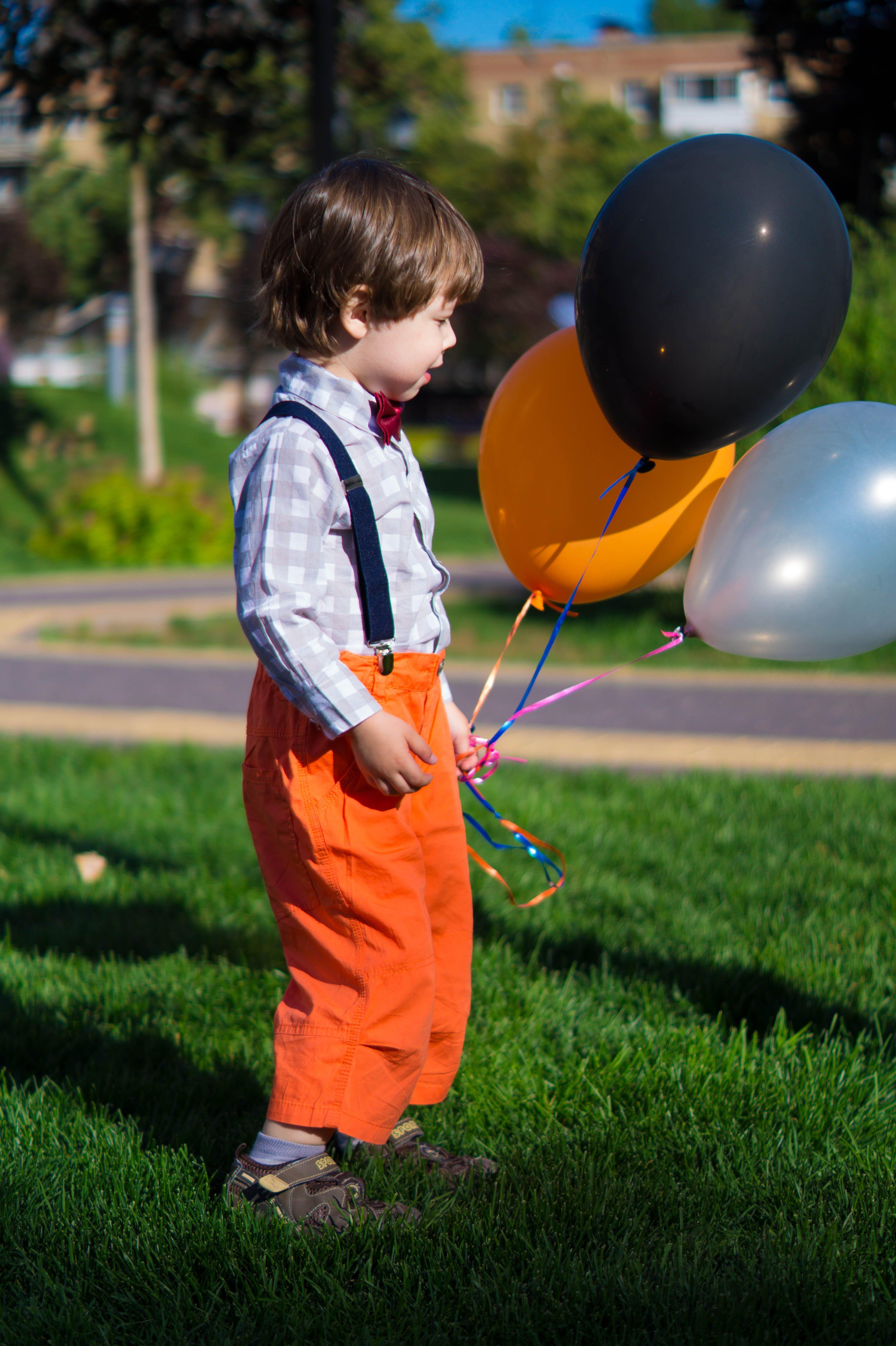 Boy Holding Three Balloons